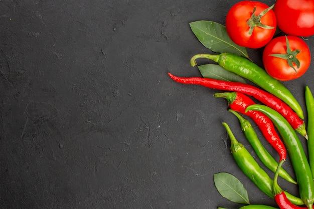 Metade superior vista pimentões vermelhos e verdes quentes e folhas de louro de tomate no lado direito do fundo preto