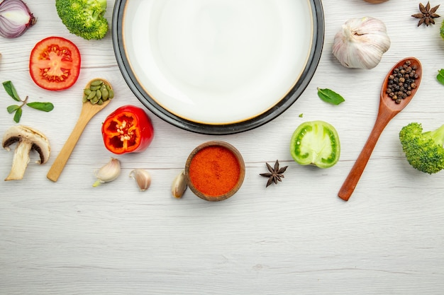 Metade superior vista prato branco tomate verde pimenta vermelha em pó em uma tigela pimenta preta em colher de madeira alho anis na mesa cinza