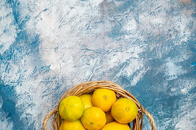 Metade superior vista tangerinas frescas em uma cesta de vime em uma superfície azul e branca com espaço de cópia