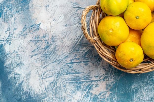 Metade superior vista tangerinas frescas na cesta de vime no espaço livre de superfície branco azul