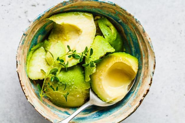 Metades de abacate descascadas em uma tigela cozinhando guacamole