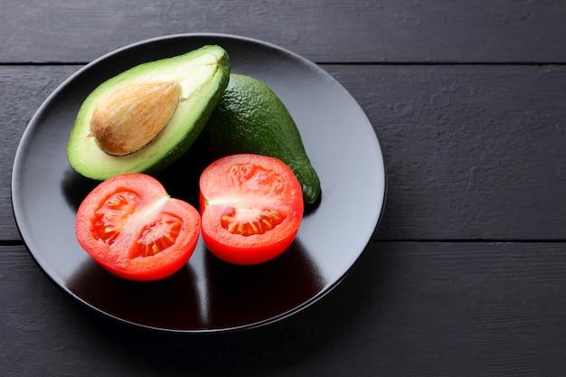 Metades de abacate e tomate em fundo preto.