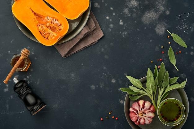 Metades de abóbora crua orgânica com folha de sálvia, alho pimenta multicolorido, mel, sal e pimenta em ardósia preta, pedra ou fundo de concreto. fundo de comida. vista superior com espaço de cópia.