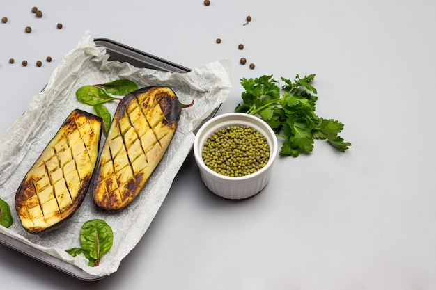 Metades de berinjela assada em paletes. folhas de salsa e feijão mungo em uma tigela na mesa.