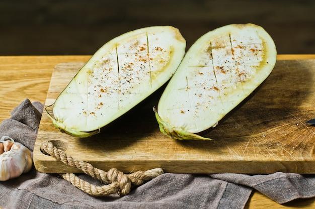 Metades de berinjela crus o conceito de cozinhar comida vegan