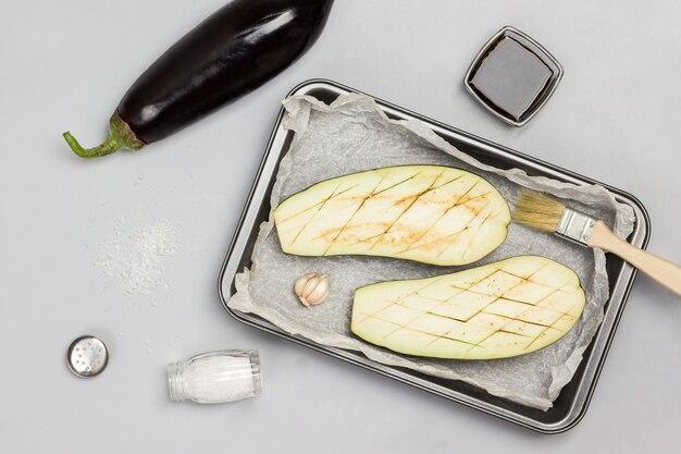 Metades de berinjela no palete sal de berinjela inteira e molho na mesa