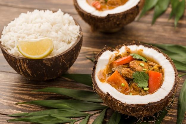 Metades de coco com ensopado e arroz