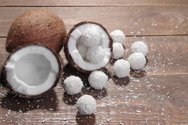 Metades de coco com lascas de coco e doces de coco em um fundo de madeira marrom