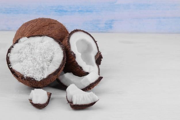 Metades de coco com raspas de coco e pequenos pedaços de coco em um fundo branco de madeira.