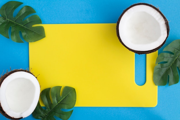 Metades de coco e placa de cozinha amarela em azul