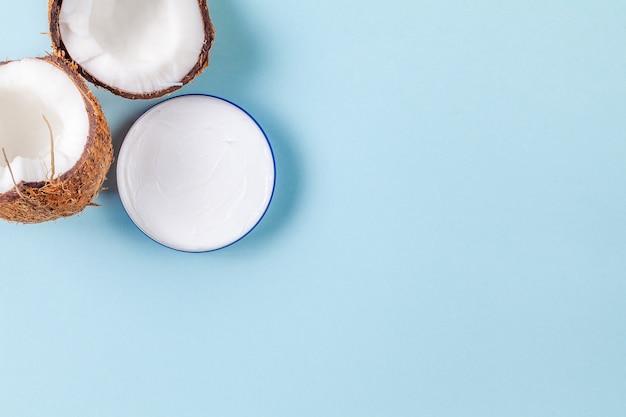 Metades de coco picado sobre fundo azul com pote de creme