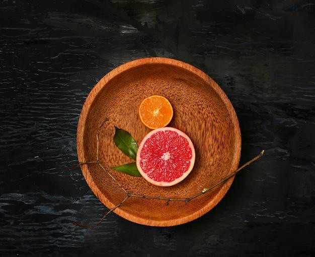 Metades de frutas cítricas de toranja na placa de madeira