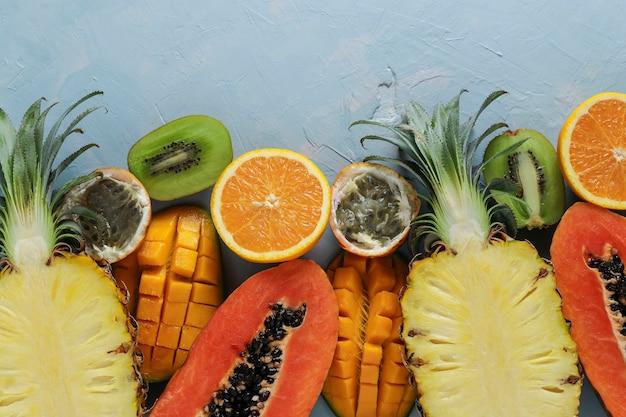 Metades de frutas tropicais: mamão, manga, abacaxi, kiwi, laranja e maracujá em uma superfície azul clara, vista superior, formato horizontal