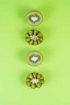Metades de kiwis verdes frescos em um fundo verde, frutas coloridas apresentam, vista superior