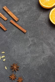 Metades de laranja e especiarias em preto. fundo de comida. postura plana. copie o espaço