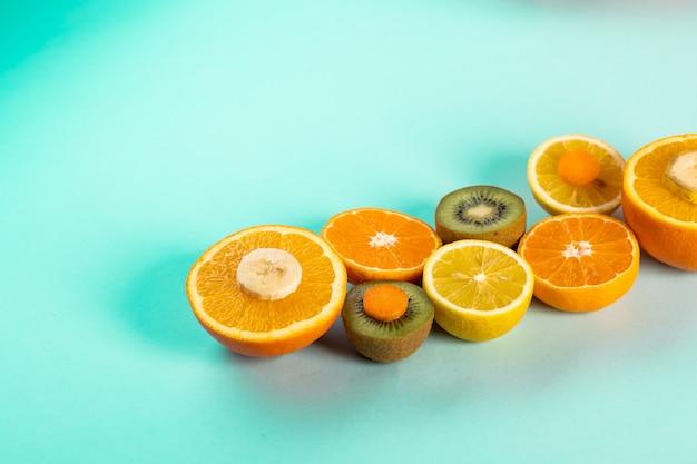 Metades de laranjas kiwi e limões em uma mesa azul