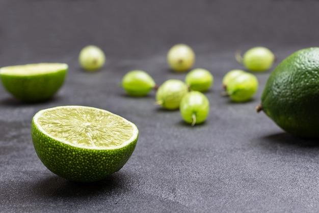 Metades de limão e bagas de groselha em fundo preto. fechar-se. proteção natural contra resfriados.