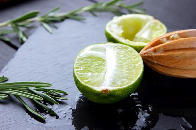 Metades de limão e espremedor de frutas de madeira na placa de ardósia. limão e alecrim. suco de limão fresco flui sobre a placa de pedra. comida saudável