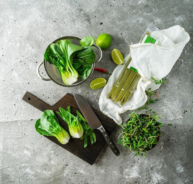 Metades do bok choi do bebê, macarronetes crus do chá verde, cais, brotos verdes no fundo cinzento. vista superior, imagem quadrada