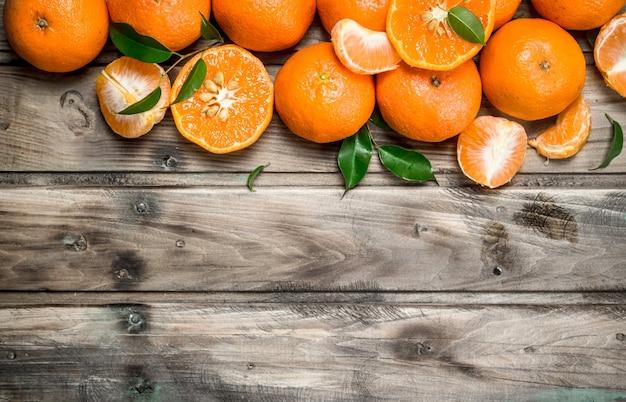 Metades e tangerinas inteiras. na mesa de madeira