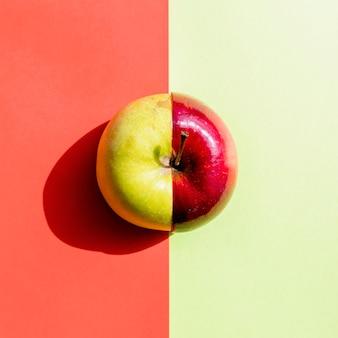 Metades planas leigos verdes e vermelhas de maçãs