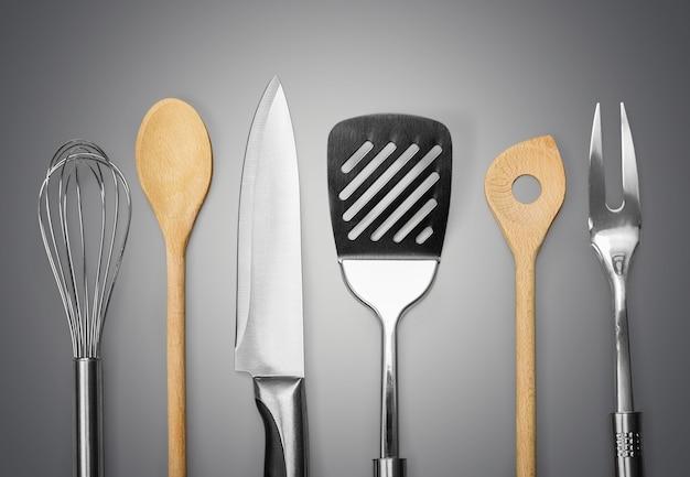 Metal de cozinha e utensílios de madeira no fundo