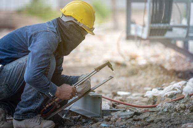 Metal de solda de trabalhador industrial com muitas faíscas afiadas