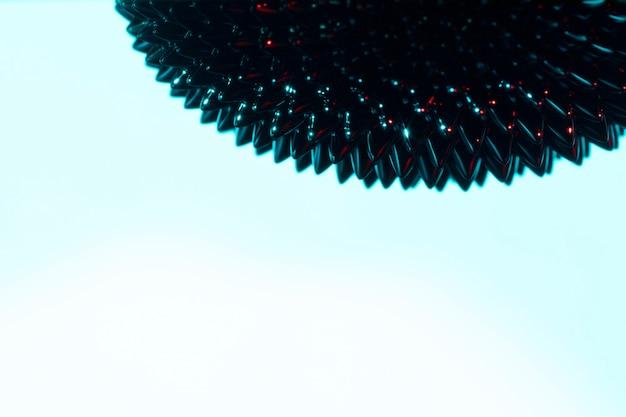 Metal líquido ferromagnético azul espetado com espaço da cópia