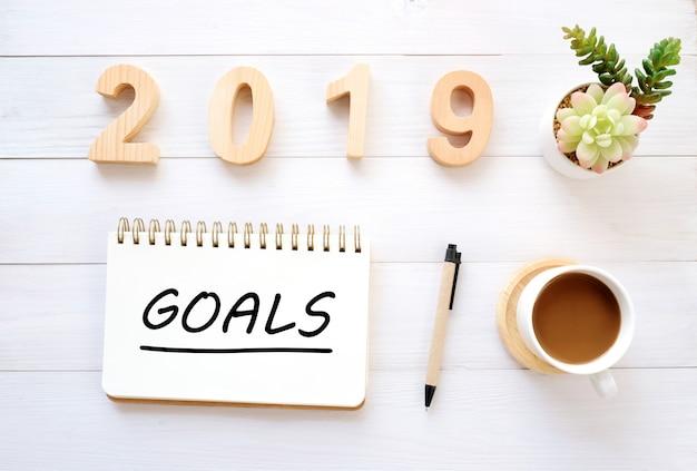 Metas de 2019 em papel de caderno no fundo de mesa de escritório, sinal de bandeira