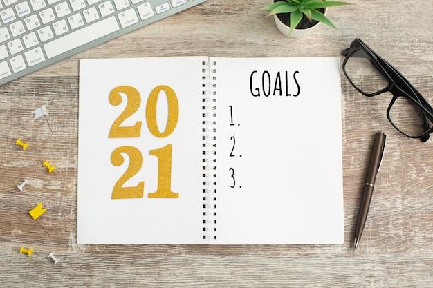 Metas de ano novo listam 2021 na mesa de madeira.