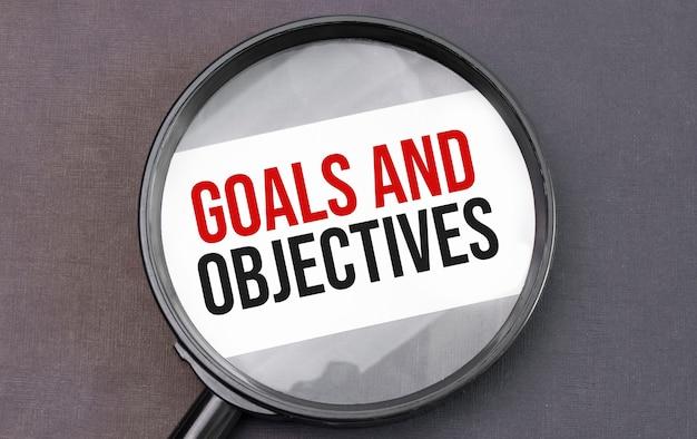 Metas e objetivos palavra no papel através de lentes de aumento.