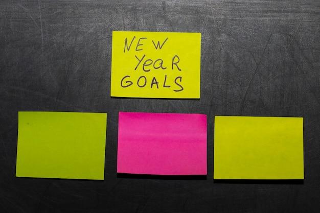 Metas ou resoluções de ano novo - notas adesivas coloridas em um quadro negro