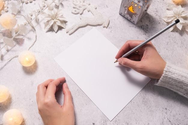 Metas, planos, lista de tarefas para o ano novo mulher com as mãos segurando um lápis de papel vazio na maquete de natal