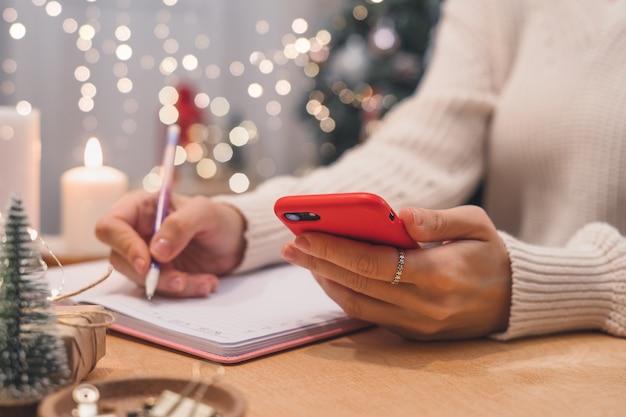 Metas, planos, tarefas e lista de desejos para o conceito de natal de ano novo escrevendo no caderno