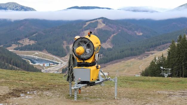 Metralhadora, canhão de neve para a produção de neve artificial nas montanhas, preparação para esquiar. faça neve. a produção de neve por bombeamento de água e ar comprimido é usada em estações de esqui.