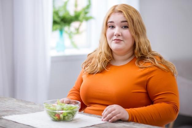 Meu almoço. alertar mulher obesa sentada à mesa e tomando café da manhã saudável