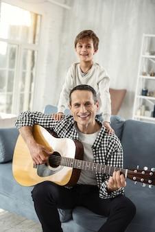 Meu amoroso papai. homem de cabelos escuros atraente, sorrindo e tocando violão, com o filho atrás dele no sofá