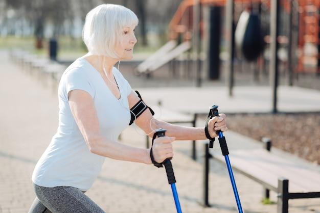 Meu bom dia. alerta mulher loira sorrindo e usando muletas durante o exercício