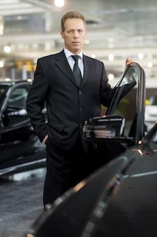 Meu carro novo. homem confiante de cabelos grisalhos em trajes formais, segurando a mão na porta do carro aberta e olhando para a câmera