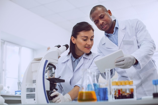 Meu colega. feliz e experiente cientista trabalhando com um microscópio e discutindo o trabalho com seu colega