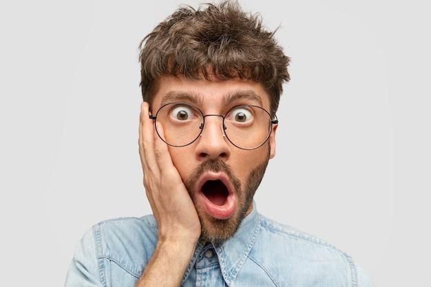 Meu deus, o que eu fiz! jovem assustado surpreso com a barba por fazer toca a bochecha e abre a boca, ficando chocado