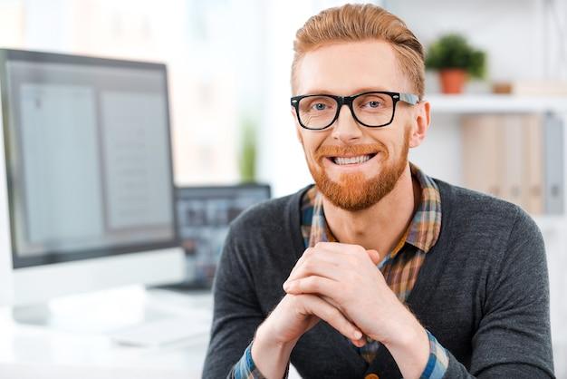 Meu espaço para criar. jovem bonito barbudo com óculos olhando para a câmera e sorrindo enquanto está sentado em seu local de trabalho