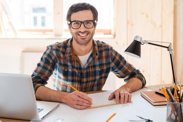 Meu espaço para criar. jovem bonito desenhando o projeto e sorrindo para a câmera enquanto está sentado em seu local de trabalho
