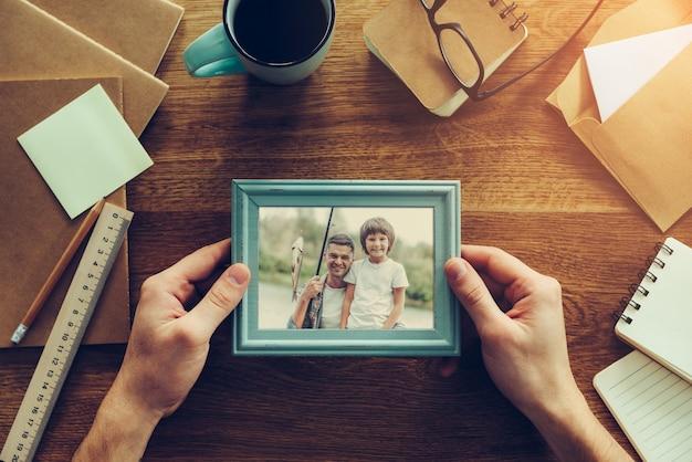 Meu filho é minha inspiração. close-up de um homem segurando uma foto com o filho pescando sobre uma mesa de madeira com diferentes coisas da chancelaria espalhadas pelo local