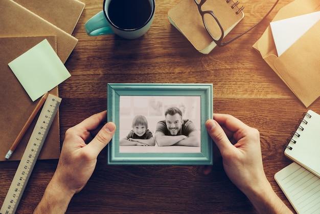 Meu filho é minha inspiração. close-up vista superior de um homem segurando uma foto dele e de seu filho sobre uma mesa de madeira com diferentes coisas da chancelaria ao redor