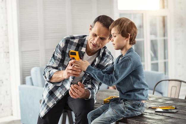 Meu filho. homem bonito e sério de cabelos escuros mostrando instrumentos para seu filho enquanto está sentado na mesa e o filho dele sentado perto dele