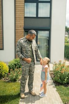 Meu herói americano. filha pequena e atraente perto de seu herói americano voltando para casa