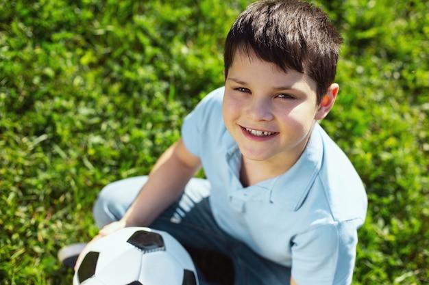 Meu jogo favorito. menino alegre de cabelos escuros sorrindo e sentado com sua bola de futebol