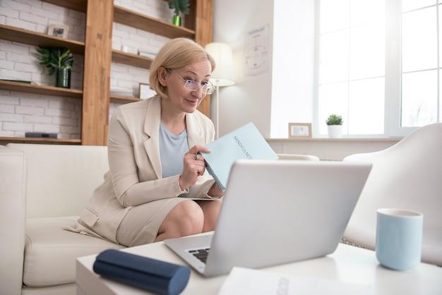 Meu livro. mulher de negócios bem sucedida e madura olhando para a tela enquanto carrega o livro