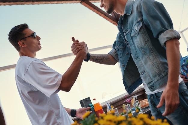 Meu melhor amigo, dois homens jovens e bonitos, apertando as mãos em pé no telhado